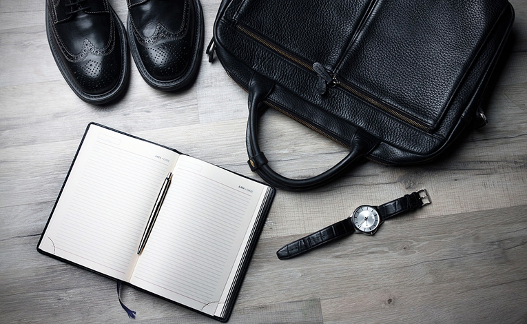 Briefcase, shoes, watch, and notebook