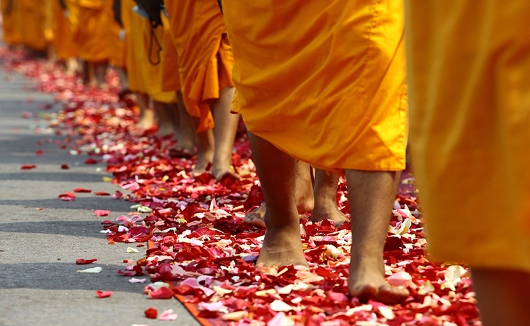 Thai monks walking on flower petals