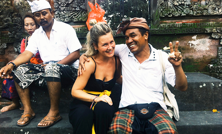 A volunteer with a Balinese man at Tirta Empul in Bali