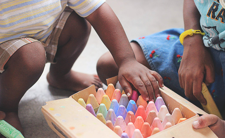 Children organizing chalk in a container