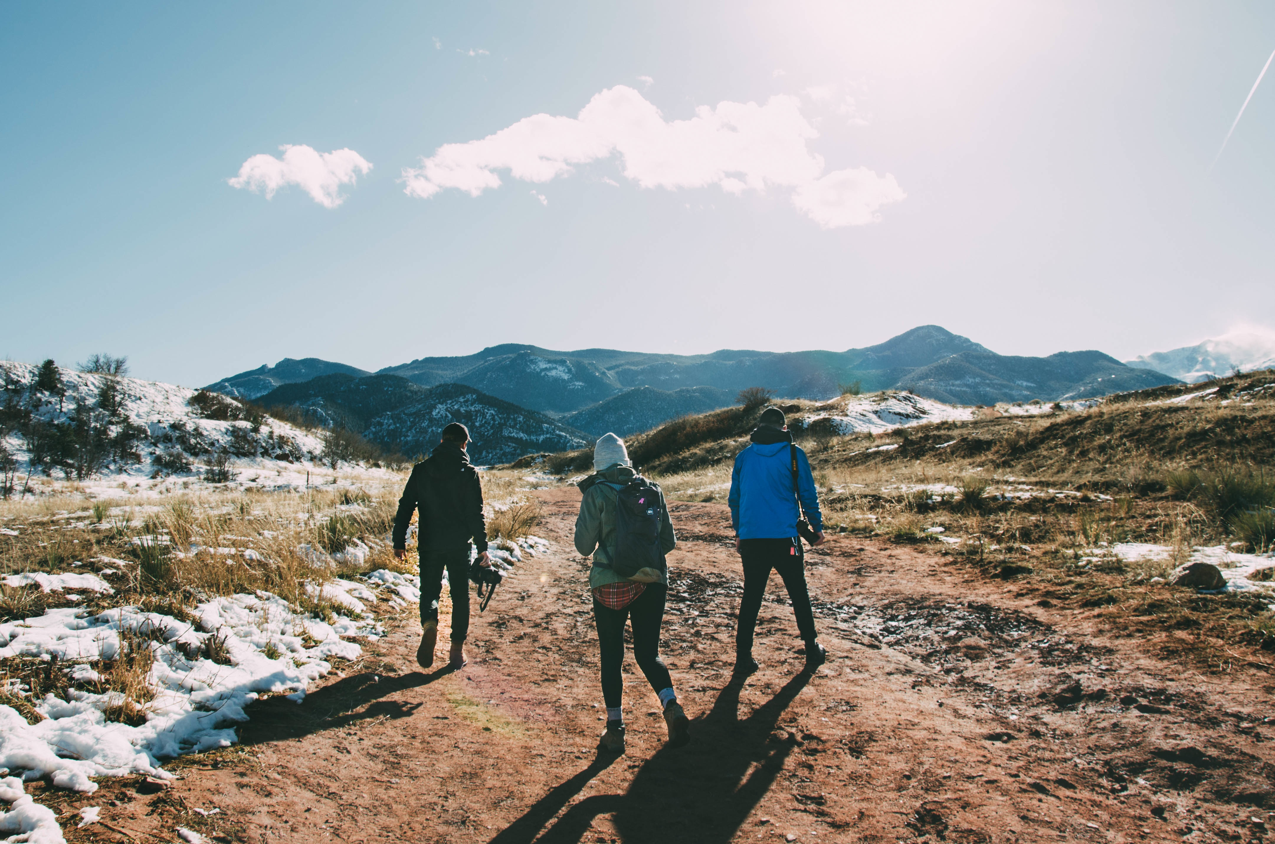 three hikers heading into the mountains with their cameras