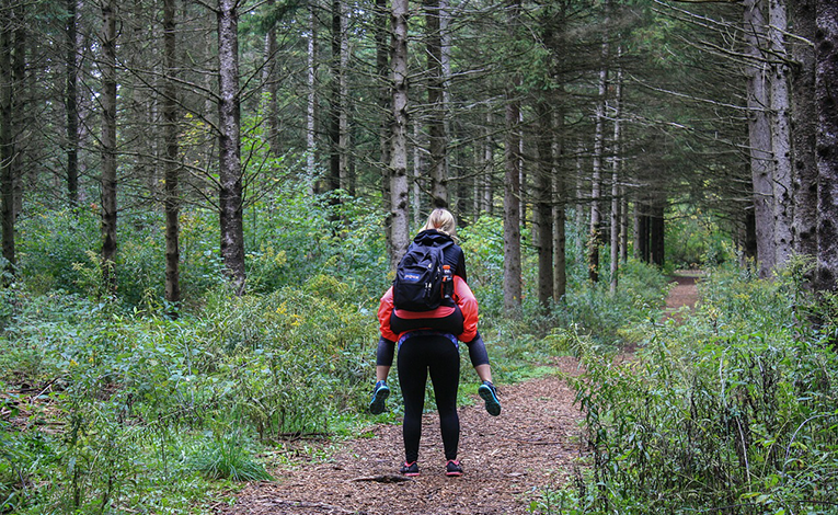 A girl giving her friend a piggy-back-ride in a forest
