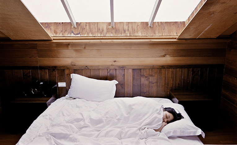Girl sleeping in a bed with white sheets
