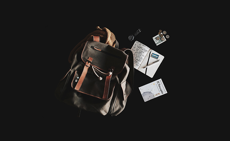 black rucksack with scattered items/accessories.