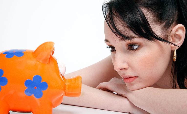 Woman staring at piggy bank.