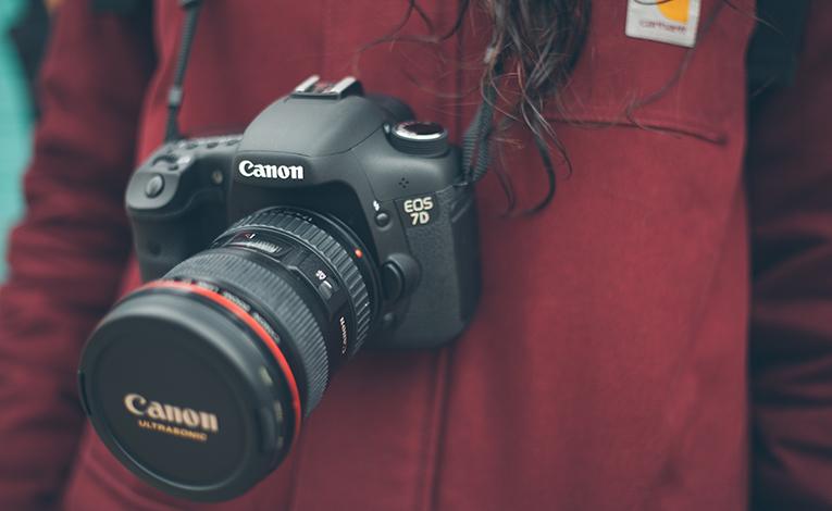 Close-up of Canon DSLR camera around a girls neck