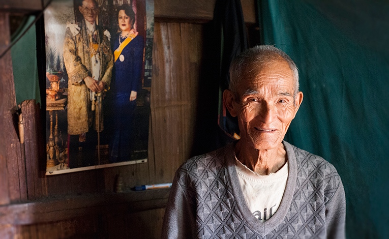 Old Thai man in front of a photo of the Thai King and Queen