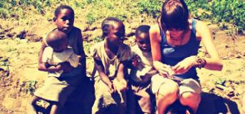 Volunteer in Kenya helping a child fix a toy