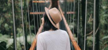Girl walking across a suspension bridge