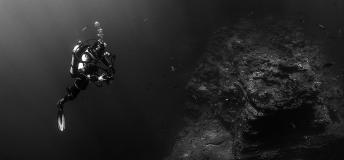 Scuba diver photographing a rock formation under water