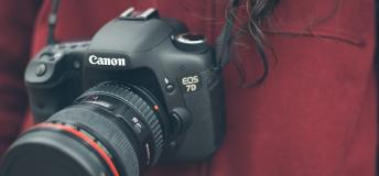 Close-up of Canon DSLR camera around a girl's neck