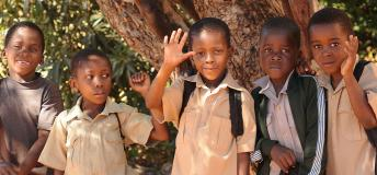 Young school children in Zimbabwe waving