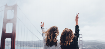 Two women posing in front of the golden gate bridge in the foggy