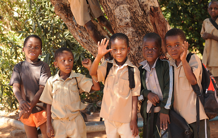 Young school children in Zimbabwe waving
