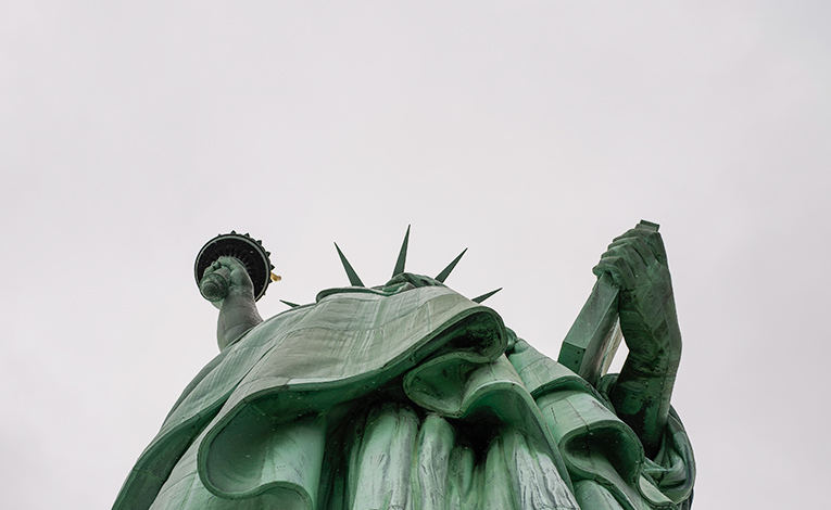 Person looking up at the Statue of Liberty